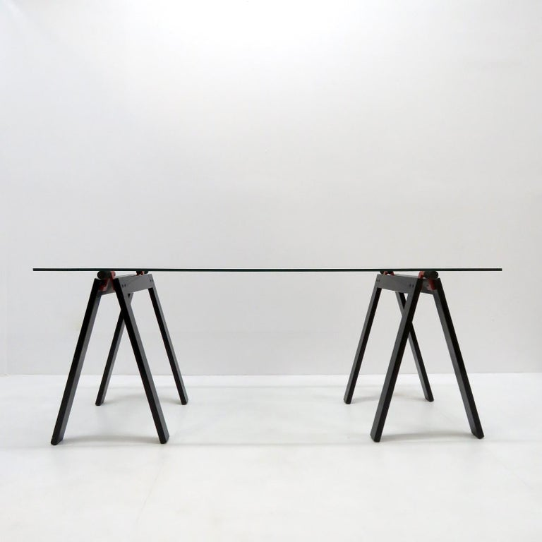 Gaetano working table by Gae Aulenti for Zanotta with original glass top, supported by two black and red enameled metal folding working horses alike base. Documented: see Repertorio Italian design book at page # 385.