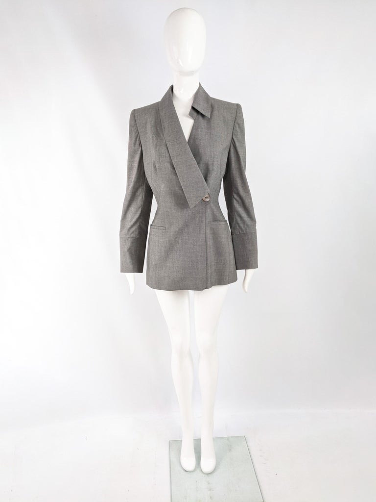 A chic vintage womens blazer from the 90s by luxury Italian fashion designer, Gai Mattiolo. In a grey virgin wool and spandex with an asymmetric collar, mother of pearl buttons on the front and sleeves and small shoulder pads that give an edge to