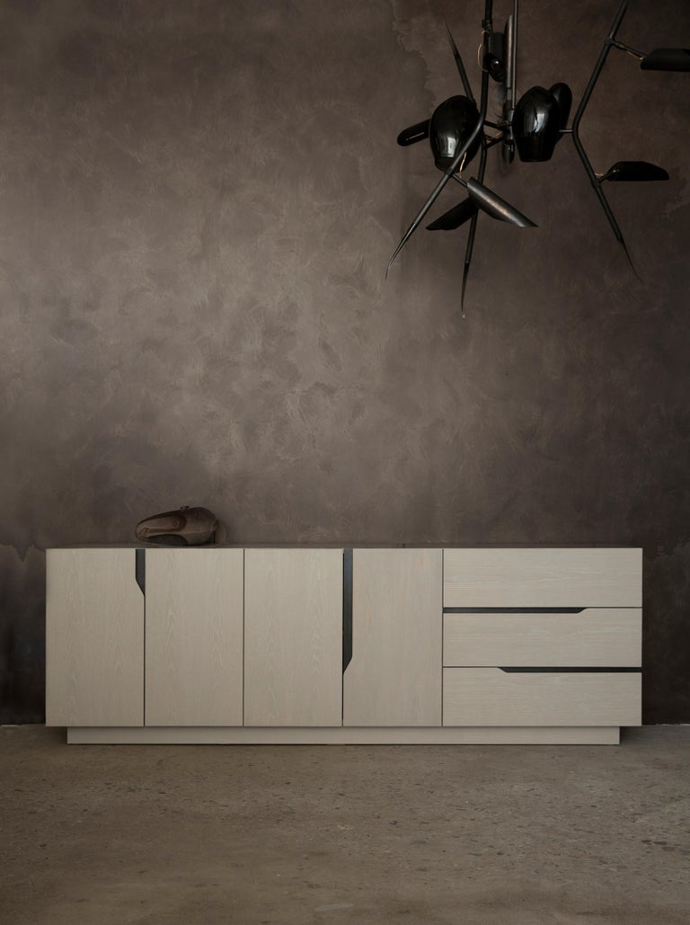 Inspired by the Greek legend, the Gaia credenza's all-wood body rests on the earth, from which it draws its strength. The solid, monolithic structure rises from the ground while the lines of the front face play with the horizontality of the