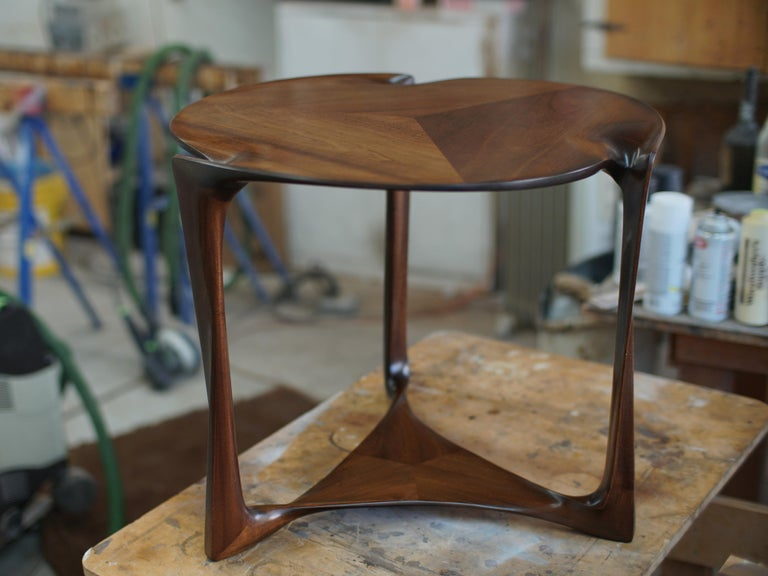 The Classic geometry of this little table, a round top over a triangular shelf or stretcher assembly, supported by three legs, is given a sculpted, organic form employing traditional carving techniques not seen since the great masters of Art