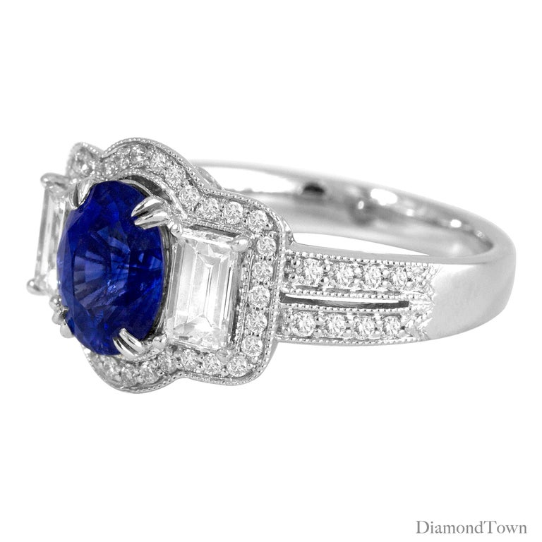 This gorgeous ring has a GAL Certified Oval Cut Sapphire center measuring 1.44 carats, flanked by two baguette diamonds and surrounded by a halo of round white diamonds. A double row of round diamonds decorate the side shank.  Center: 1.44 Carat