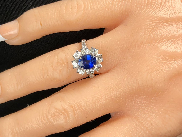 This handcrafted ring features a 1.89 carat Oval Cut Ceylon Sapphire center, surrounded by a halo of eight oval cut diamonds. Additional round diamonds trail down the side shank, bringing the total diamond weight to 1.53 carats.  Ring size 6.5, with