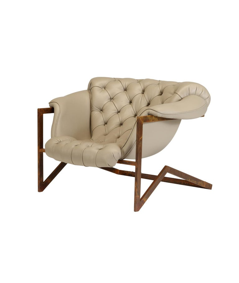 An elegant mix of materials and styles, this stunning armchair features a cantilever base made of iron with a brown