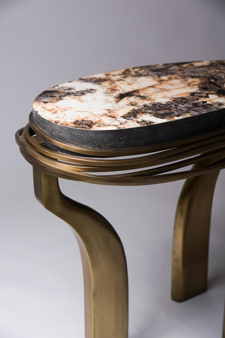 The galaxy side table in large is an iconic Kifu Paris piece. Whimsical, sculptural and bold this piece makes the ultimate accent piece in any space. The intricate bronze-patina brass rings encircle the semi-precious stone (Hwana) inlaid top. The