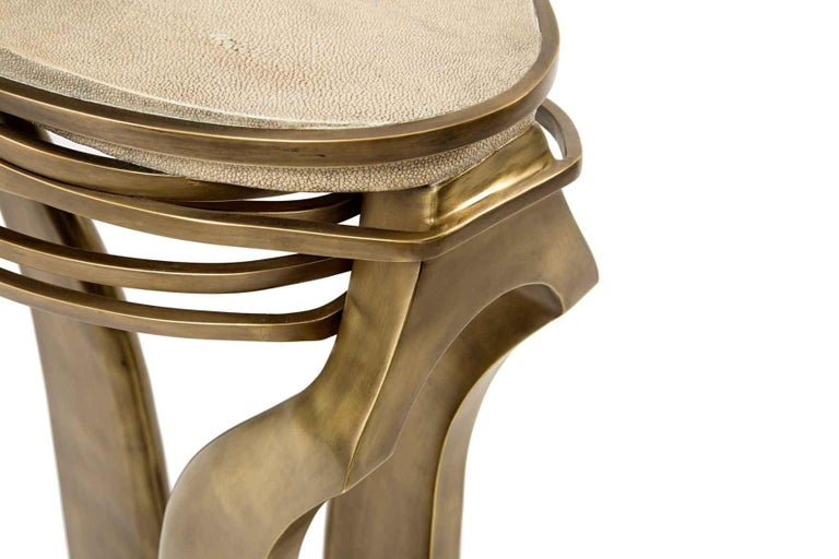 The galaxy side table in small is an iconic Kifu Paris piece. Whimsical, sculptural and bold this piece makes the ultimate accent piece in any space. The intricate bronze-patina brass rings encircle the cream shagreen amorphous-shaped inlaid top.