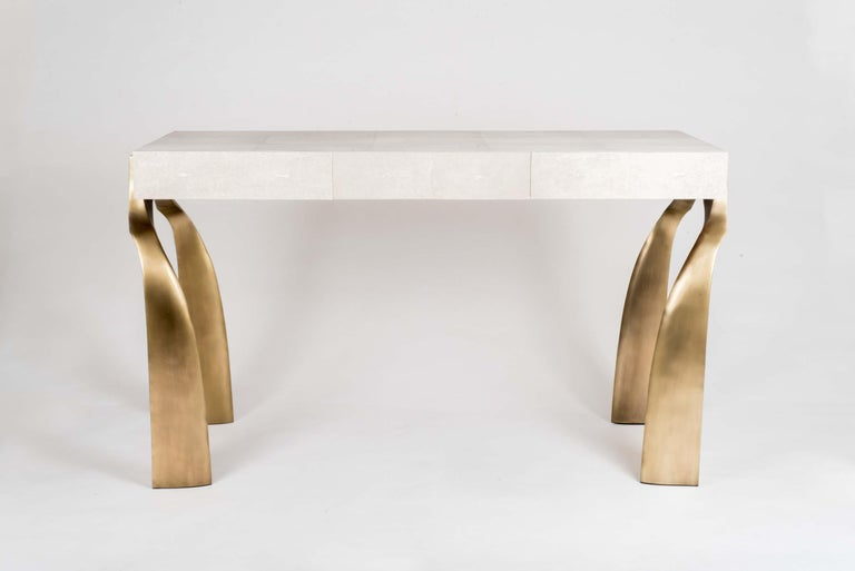 The Galaxy writing desk in cream shagreen, is a classic and sculptural piece with its beautifully shaped bronze-patina brass legs. This piece has three wood-veneer drawers, add a mirror and this desk becomes a vanity. The shagreen is hand-dyed by