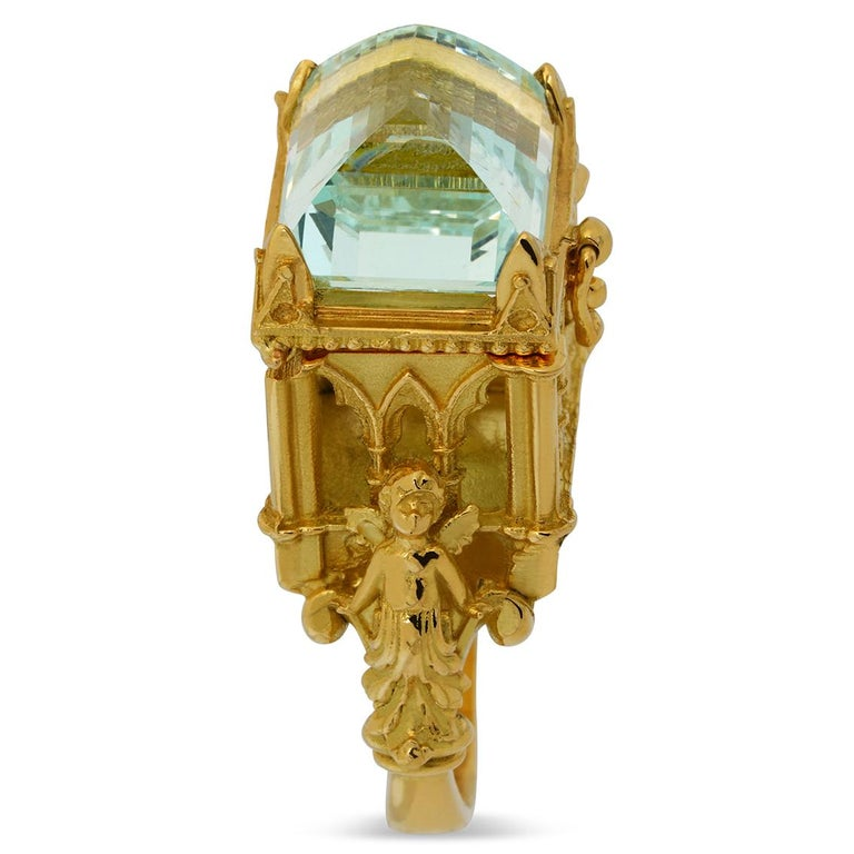 Flanked by two guardian angels and sitting aloft a gorgeous soft rounded split shank, this stunning gothic cathedral ring exquisitely handcrafted in 18kt yellow gold features a latched chamber topped with a divine 8.66 carat powder blue 12.45mm (L)