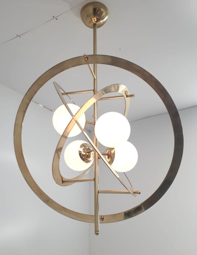Italian modern chandelier with glossy white Murano glass globes mounted on polished brass frame / Designed by Fabio Bergomi for Fabio Ltd / Made in Italy 4 lights / E12 or E14 type / max 40W each Measures: Diameter 31.5 inches / Height 47 inches