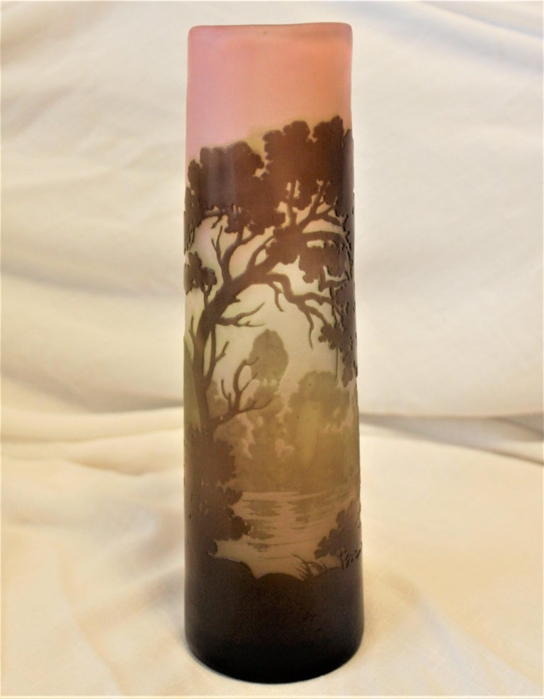 This antique signed Galle vase was made in France in approximately 1900 in the period Art Nouveau style. The vase in done in multiple layers of colored glass that's been etched, cut and polished to reveal a country landscape with a brook in the