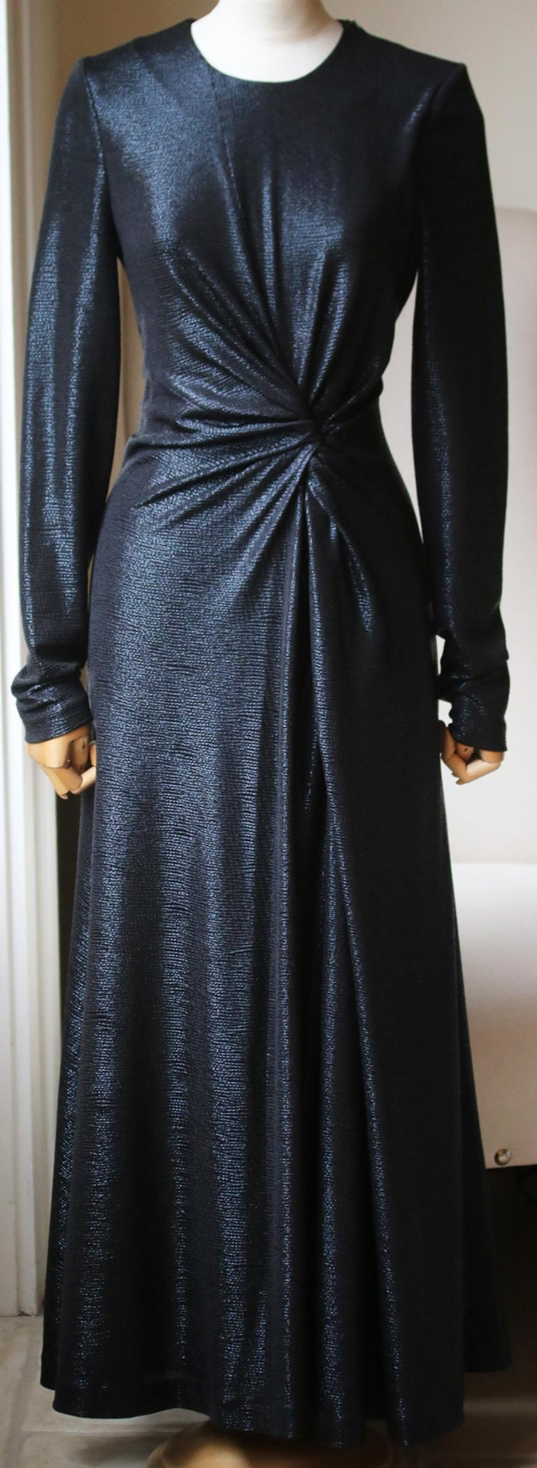 Shimmering metallic dress with a twist-front detail that drapes down to a swinging skirt that has a thigh-high side slit. Round neck. Long sleeves. Concealed zip closure. In black. 95% polyester, 5% spandex.   Size: UK 10 (UK 6, FR 38, IT