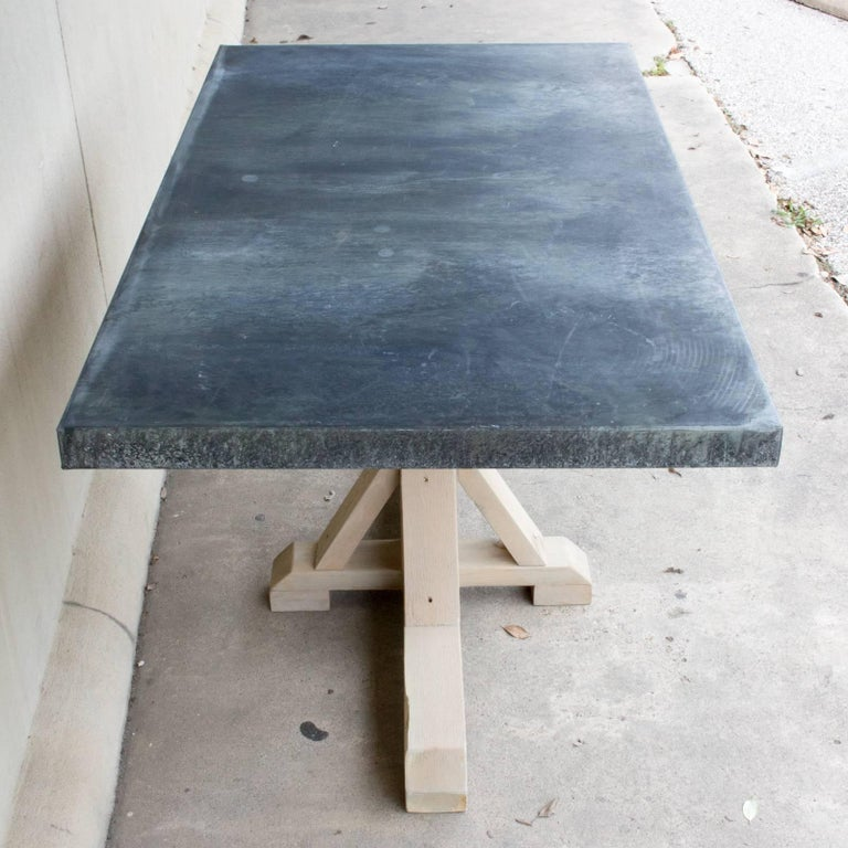This handmade table is constructed with a wood base and galvanized zinc metal top. The pine base has been treated with a grey-toned wash to give the piece a lighter feel. Makes for a beautiful addition to your kitchen or in a breakfast nook, but