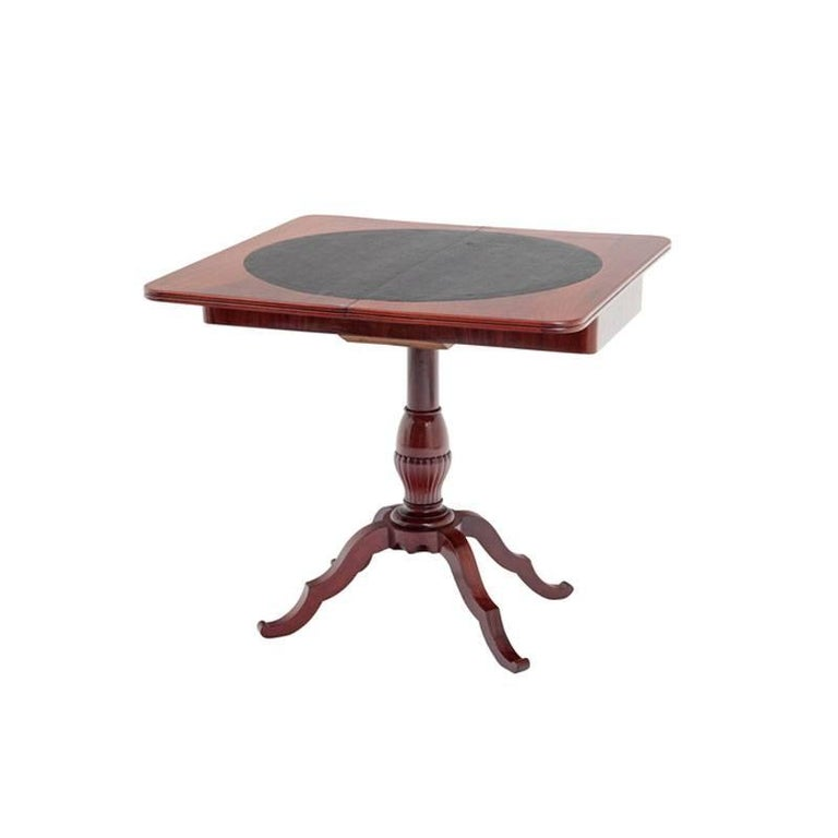 This game table stands on four wavy feet which stem from a central fluted shaft. The top of the table opens to reveal a surface fit for playing games. The playing surface is circular and covered in black leather.   Table when opened 86 x 86 cm.