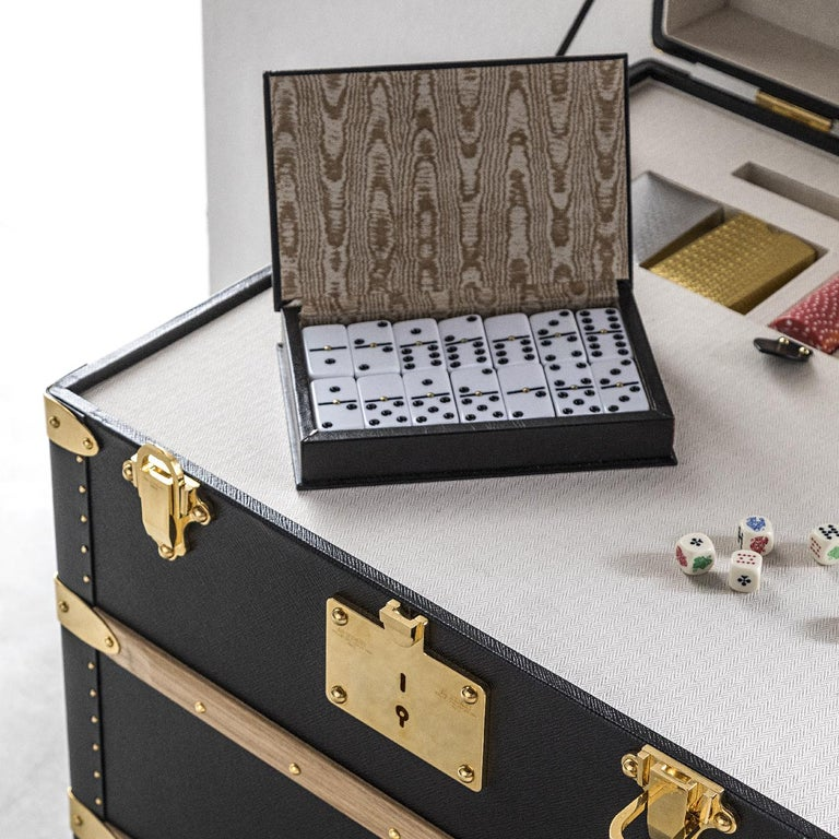 Part of the Music and Games collection, this elegant trunk combines a modern aesthetic with the old-fashioned allure of Classic board games, conveniently stored all in one place. The elegant and spacious piece includes cards and fiches games, a