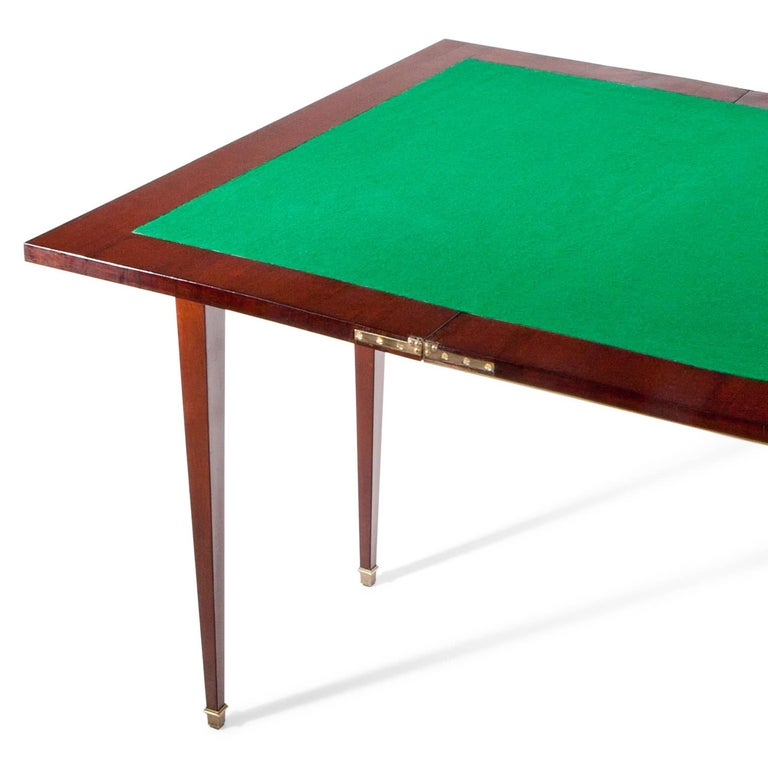 Mahogany gaming table standing on tapered feet with brass sabot. The fillings and the table edge are framed with brass moldings. The inner surface of the table is lined with green felt. Size folded out: 77 x 94 x 94 cm.