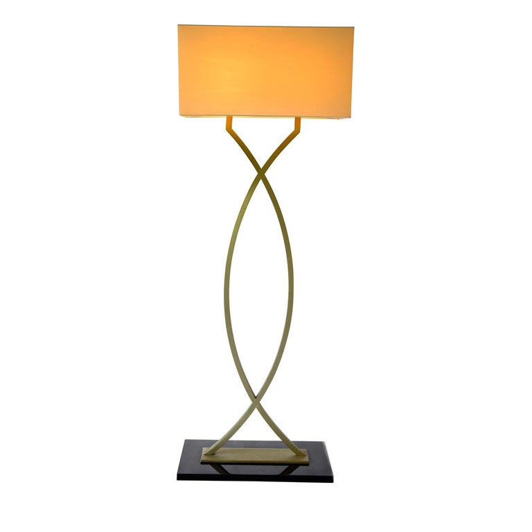 Standing tall on a goatskin base in a dark mocha tone, the gamma brass floor lamp sets an elegant tone in a traditional or contemporary living room. The lamp features an original stem, with two gently arching pieces of brass with a satin finish,