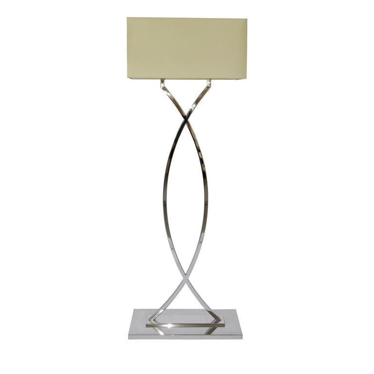 Glistening from the floor to its drum shade, the Gamma nickel floor lamp is pure sumptuous elegance for traditional and modern living rooms. Characterized by its gently arching stem with a harmonious shape, the nickel floor lamp stands on a sturdy
