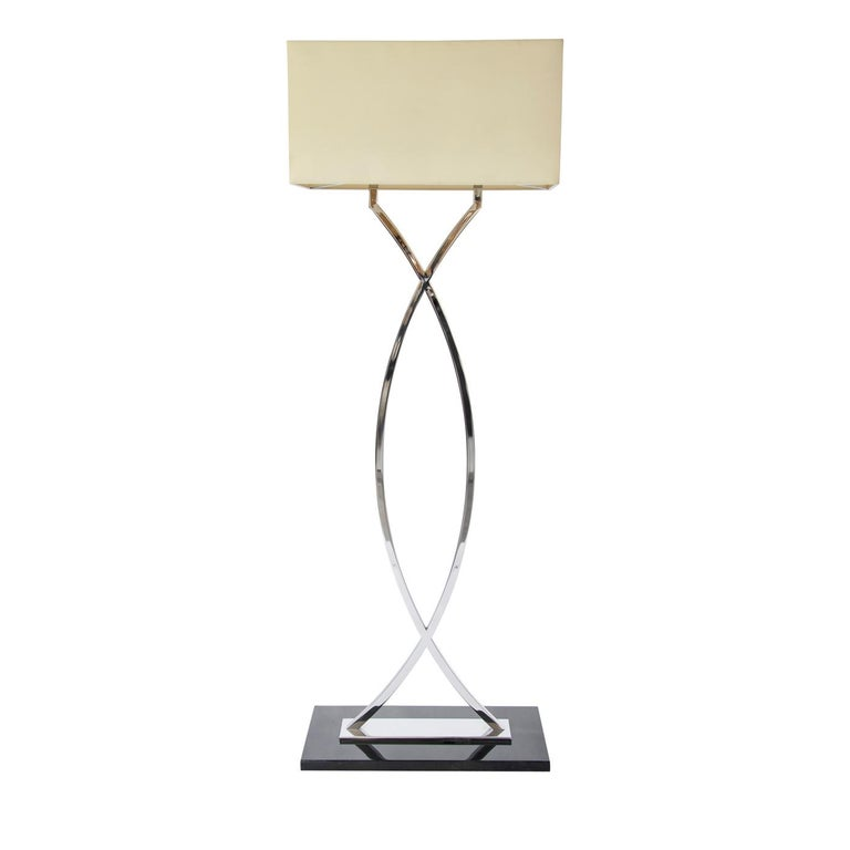 The gamma stainless steel floor lamp exudes timeless elegance. From its goatskin base with a deep teal finish to its glistening stainless steel stem, the floor lamp is an original design, perfect for traditional and contemporary living rooms or home
