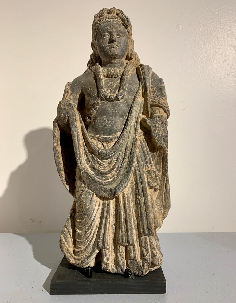 An impressive and well carved Gandharan figure of the Bodhisattva Maitreya, the Buddha of the Future, carved black schist, ancient Kingdom of Gandhara, 2nd-4th century.  Maitreya is portrayed standing upright, one knee slightly bent in