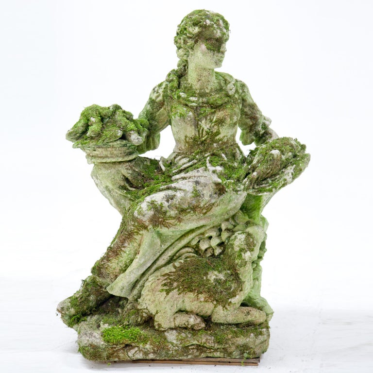 Italian pastoral figure of a poultry seller, seated on a tree trunk, with baskets full of her wares, carved Pietra di Vicenza stone. A lamb nibbles on some grass blades towards her feet. Very detailed carving, partly damaged and weathered.
