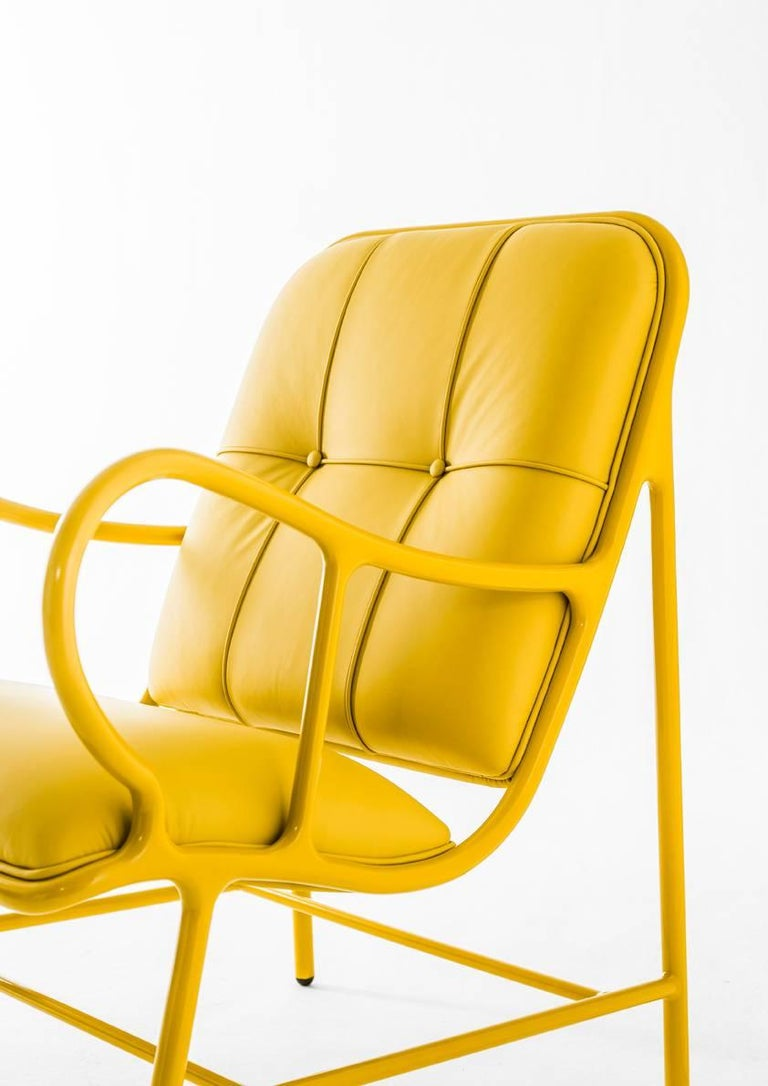 Structure in cast aluminium and laminates in extruded aluminium. Painted in high-gloss yellow (RAL 1005). Seat and backrest upholstered in leather. Piping in the same color as the structure.