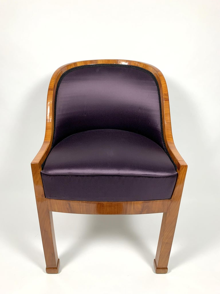 This Biedermeir style chair of walnut veneer has been fully restored- French polished, shellacked to a high gloss finish, it features high comfort, with a purple silk fabric. Lovely armchair with luxurious purple fabric. This item is in an