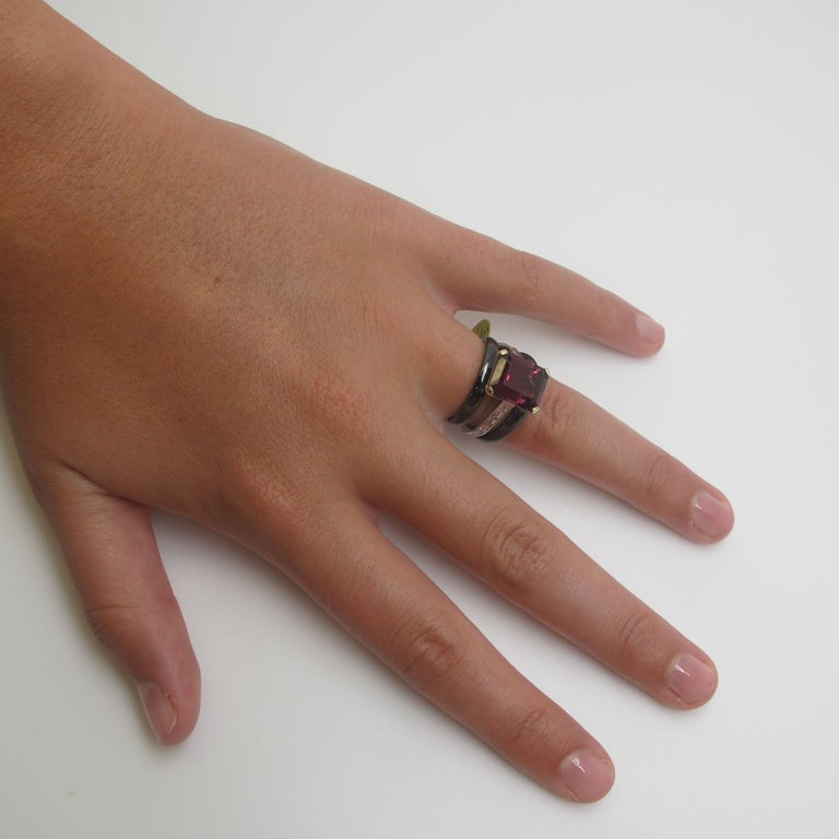 Sleek and modern! This ring design is part of our Sticks and Stones Collection featuring a sophisticated, rectangular center stone and side stones with a similarly contemporary feel. The gem rhodolite garnet showcased here is a rich, raspberry color