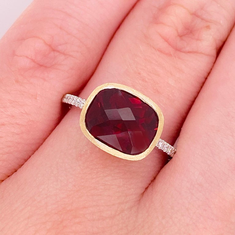 This stunning red garnet surrounded by brushed 14k yellow gold and set on a beautiful white gold band dripping with diamonds provides a look that is very modern! This ring is very fashionable and can add a touch of style to any outfit, yet it is