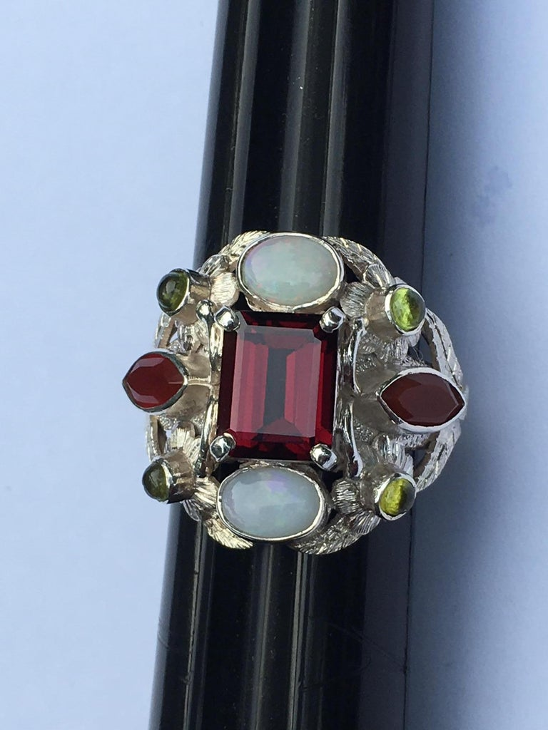 This ring is not just a ring its piece of art. Center red stone is  7 X 9 MM very clean Garnet, 6 X 8 MM oval Opal, 3 X 6 MM Marquise Carnelian and 2 MM Round  cab Peridot. This ring is created by very skilled gold and silver smith named. R.Rasile