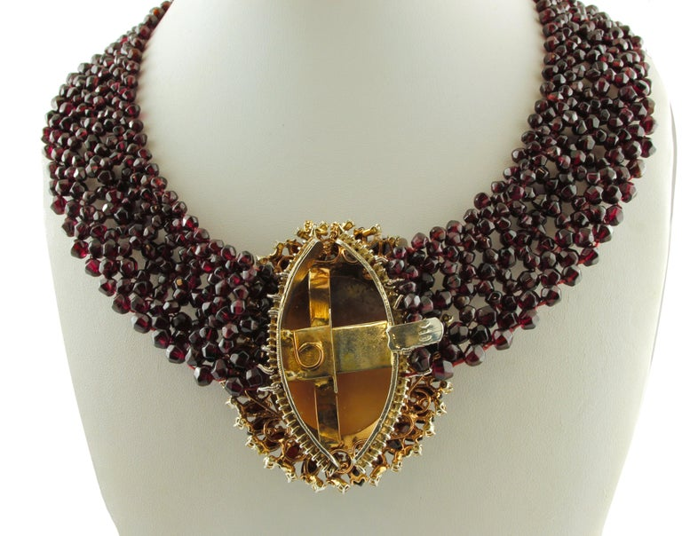 Amazing necklace in 9k rose gold and silver structure, consisting of a garnets perimeter and a central cameo representing a woman motif, surrounded by garnets and yellow topazes.  This marvelous necklace is totally handmade by Italian master