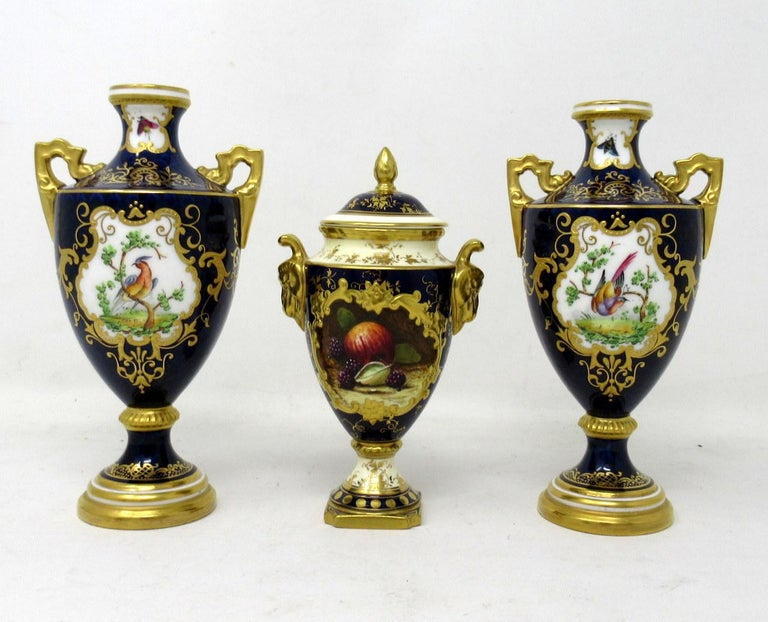 Stylish pair English Porcelain twin handle hand painted Coalport urns, late nineteenth century.  Exquisitely hand decorated depicting exotic birds, butterflies and flowers in landscape on a cobalt blue ground with lavish raised