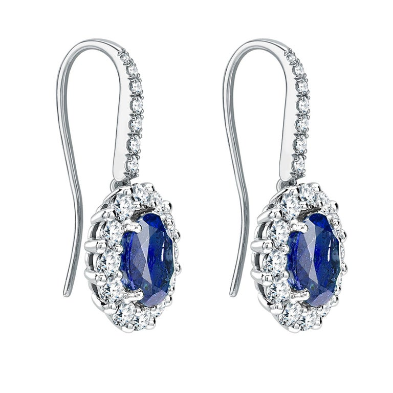 A pair of House of Garrard platinum drop earrings from the 1735 collection each set with a central oval blue sapphire weighing 1.64 carats and 1.44 carats and 38 round white diamonds weighing 1.12 carats 2 oval blue sapphires weighing 1.64 carats