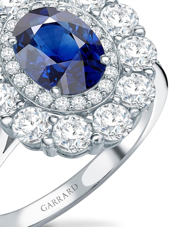 A House of Garrard platinum double cluster surround ring from the 1735 collection set with a central GIA certified oval blue sapphire weighing 1.43 carats and 58 round white diamonds weighing 1.56 carats Size: 51 / L / 5 (3/4) (Ring can be sized up