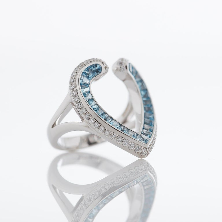 A House of Garrard 18 karat white gold ring from the 'Aloria' collection, set with round white diamonds and calibre cut aquamarines.   50 round white diamonds weighing: 0.53cts  24 calibre cut aquamarines weighing: 1.10cts  Size 54  Please note