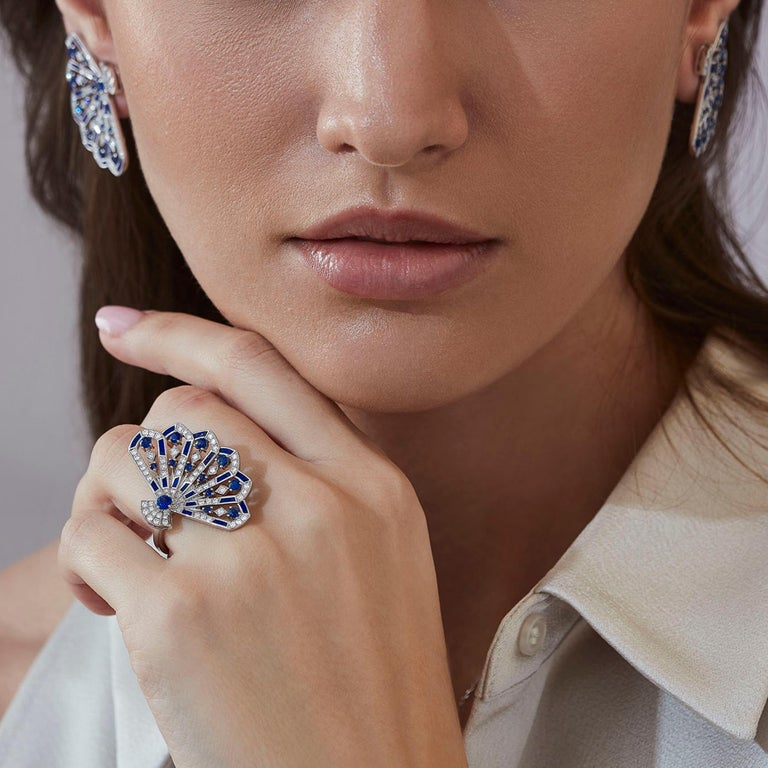 A House of Garrard 18 karat white gold 'Fanfare Symphony' ring, set with round blue sapphires, round white diamonds and lapis lazuli inlay.   13 round blue sapphires 73 round white diamonds 19 pieces of lapis lazuli inlay Size 54  Please note rings