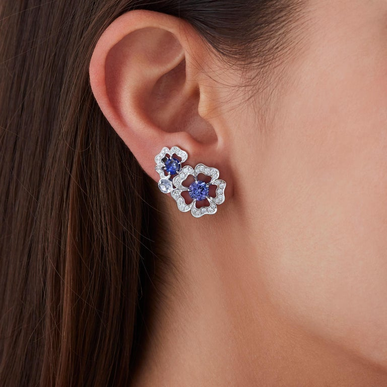 A House of Garrard pair of 18 karat white gold ear climbers from the 'Tudor Rose Petal' collection set with blue sapphires, tanzanites and round white diamonds.