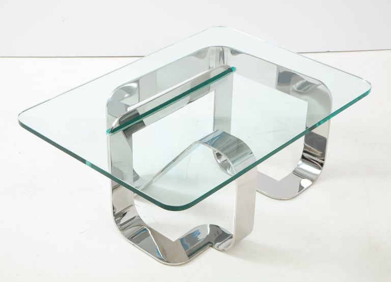 """""""Jason"""" cocktail table in stainless steel and glass by New York City designer and interior decorator Gary Gutterman. An exceptionally well-executed continuous form with the unusual feature of a segment that pierces the surface of the glass top,"""
