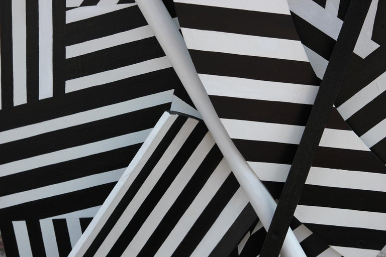 Black and white striped constructed asymmetrical wall sculpture. Attached the to surface are cut shapes including circles and half-circles painting in the same was as the wooden base along with sold black and white circular and square rods. The work