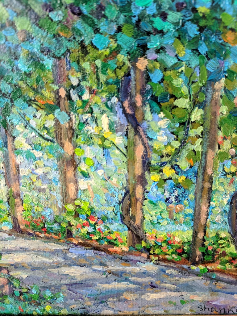 This oil painting on linen is a fine example of an American impressionist landscape by a masterful painter. The painting provides a scene of green and many-hued trees that give an embrace to a stone path. The light filtering through the leaves give