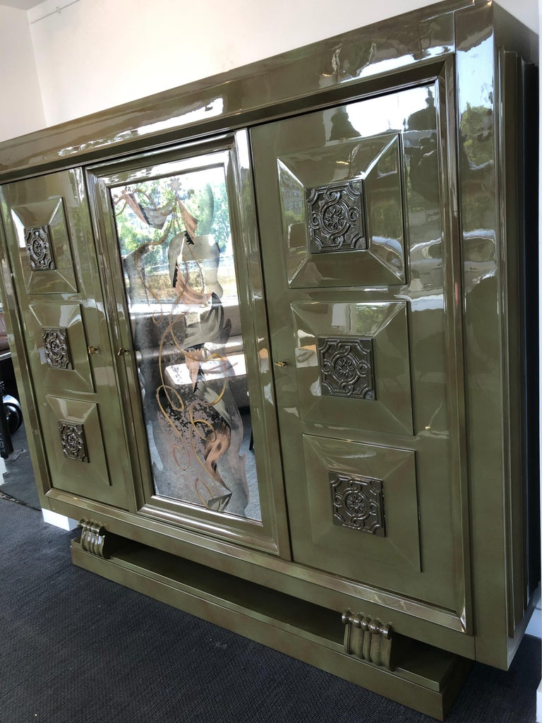 """This splendid and rare large furniture piece includes three doors with engraved signed keys from the artist Gaston Poisson, """"GP"""". This circa 1937 cabinet is made of green lacquered* mahogany and contains 12 interior shelves (three doors each with 4"""