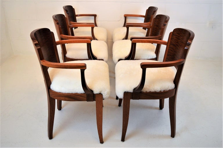 Six elegant armchairs, reupolstered with sheepskin. These solid mahogany chairs, with beautiful burl mahogany on the back-side, are created by the French designer Gaston Poisson in the early 1930s. The chairs are restored and finished in