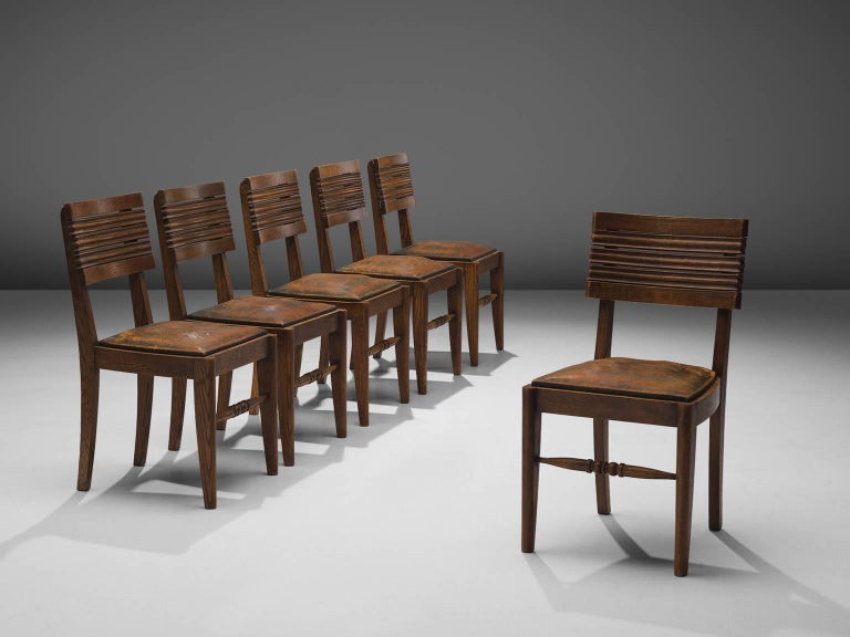 Gaston Poisson, set of six dining chairs, oak and green and brown leather, France, 1940s.  Dining chairs in solid oak, with beautiful detailed woodcarving and stunning patinated leather. The back of the chair consist of five slightly curved slats: