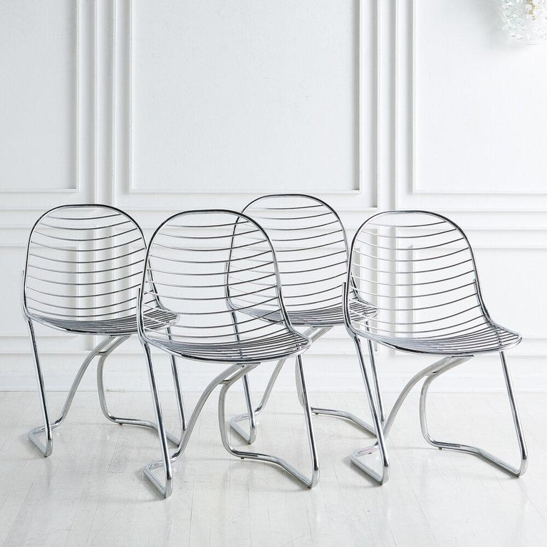 A set of four chrome dining chairs designed by Gastone Rinaldi for his family business, RIMA. Classic Italian design from the 1970s.  Dimensions: 33.5