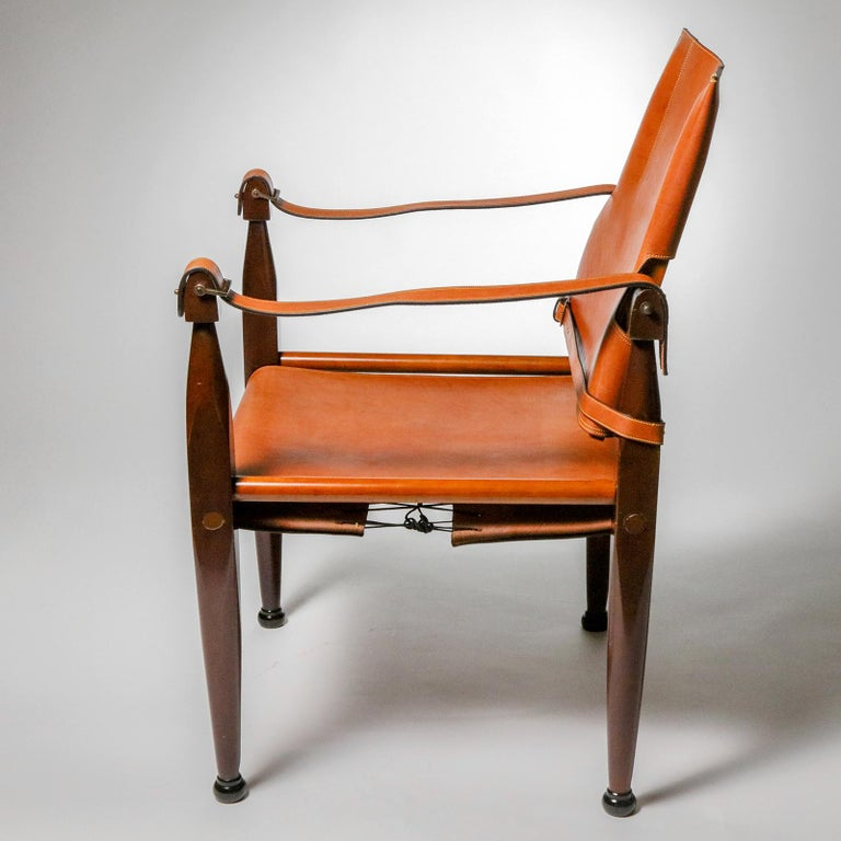 A distinctive cognac-colored leather accent chair, so-called because of the stitched bridle strap arms and leather buckle detailing that recalls the famous Spanish cowboys (gauchos). Dark maple wood frame in distressed finish completes the look.