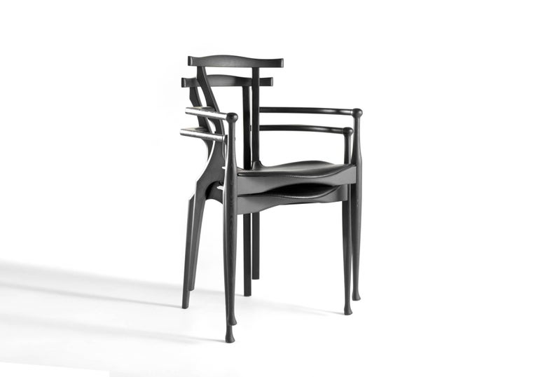 Solid ash lacquered in black with seat in black hide.