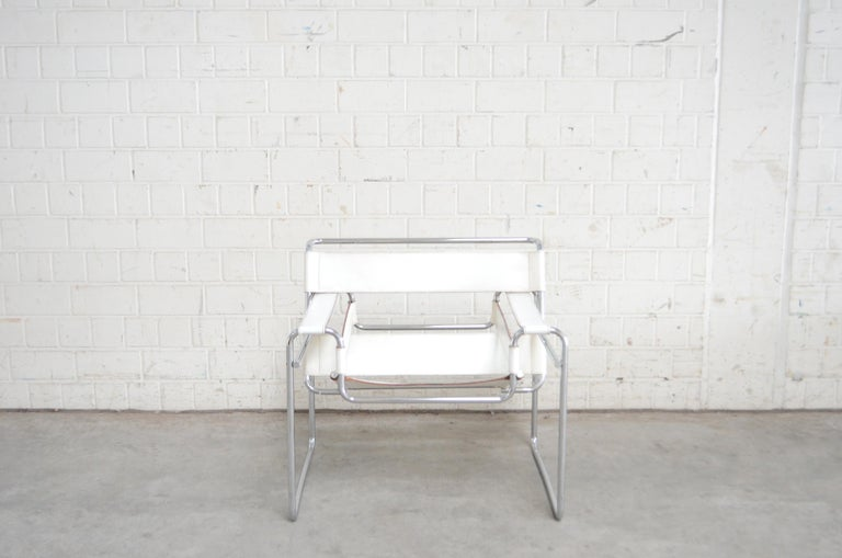 This Wassily chair, in chromed tubular steel and white leather, was designed by Marcel Breuer and produced by Gavina. It's an early edition before 68 with the stamp underneath the seat. It has some marks on the leather seat.