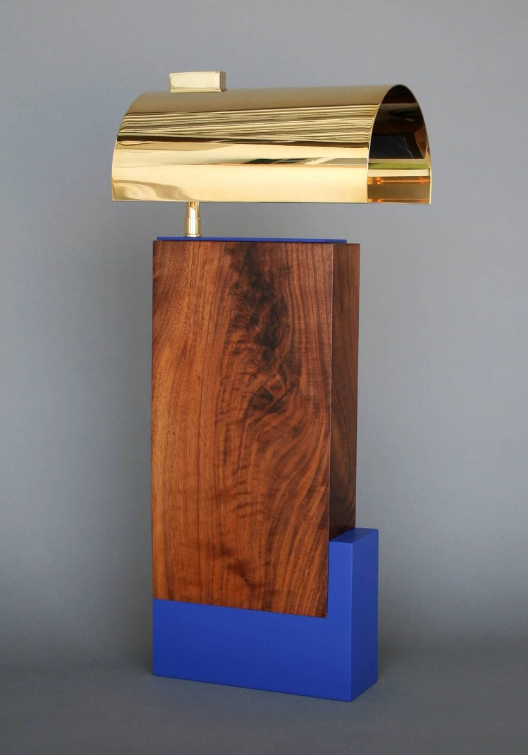 The 'Gemini' table lamp was inspired by simplicity of form, color scheme and respect of materials found in Bauhaus movement. It is shown above with a solid walnut body, a matte black or blue base and a copper or brass shade. Metal is unsealed and