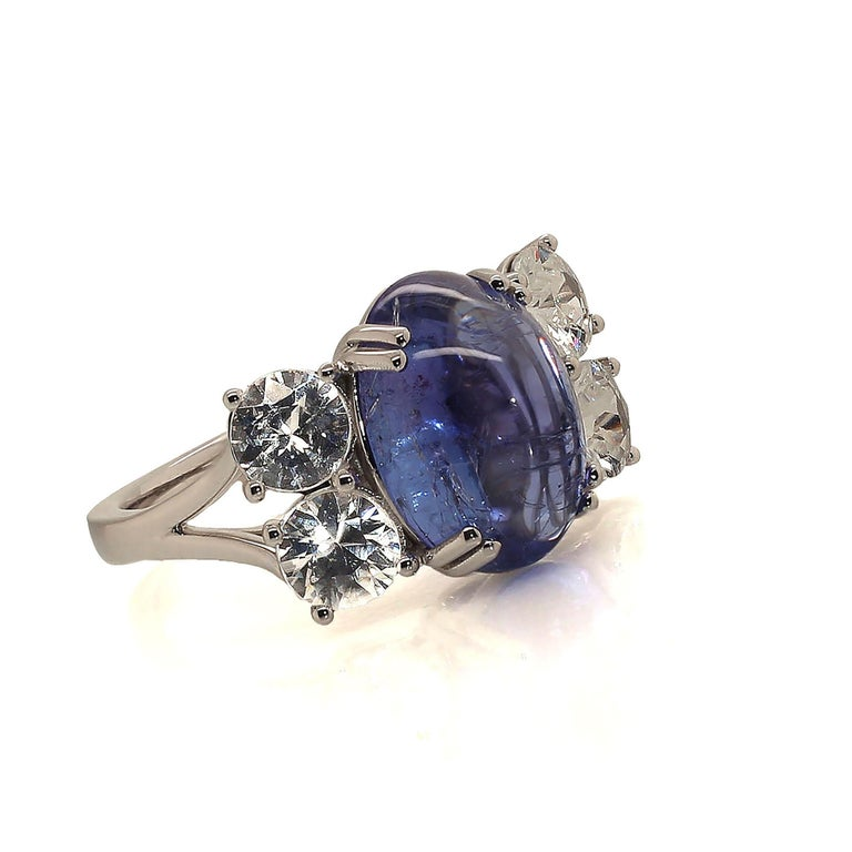 Gorgeous dinner featuring a clean sparkling blue-purply oval Tanzanite cabochon enhanced by two pairs of glittering colorless Cambodian Zircons.  This stunning flashing ring will delight wherever it goes. The hand made setting is 14K white gold four