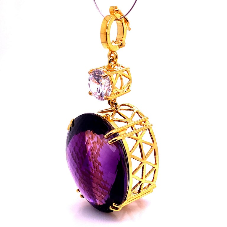 This incredible large Amethyst pendant sparkles and flashes as it moves. The 67.58 carat checkerboard table Amethyst is accented with a white Cambodian Zircon of 3.96 carats. Both gemstones sit in handmade woven baskets of gold rhodium plated