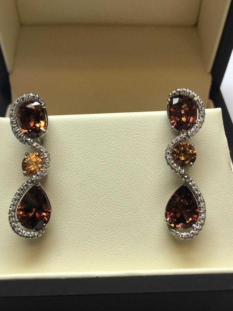 The fire in these very unique colored Tanzanian Zircon earrings surrounded by white diamonds really are a show stopper. The 12.55 carats in total weight of oval, round and pear shaped Zircons are accented perfectly with diamonds and the design of