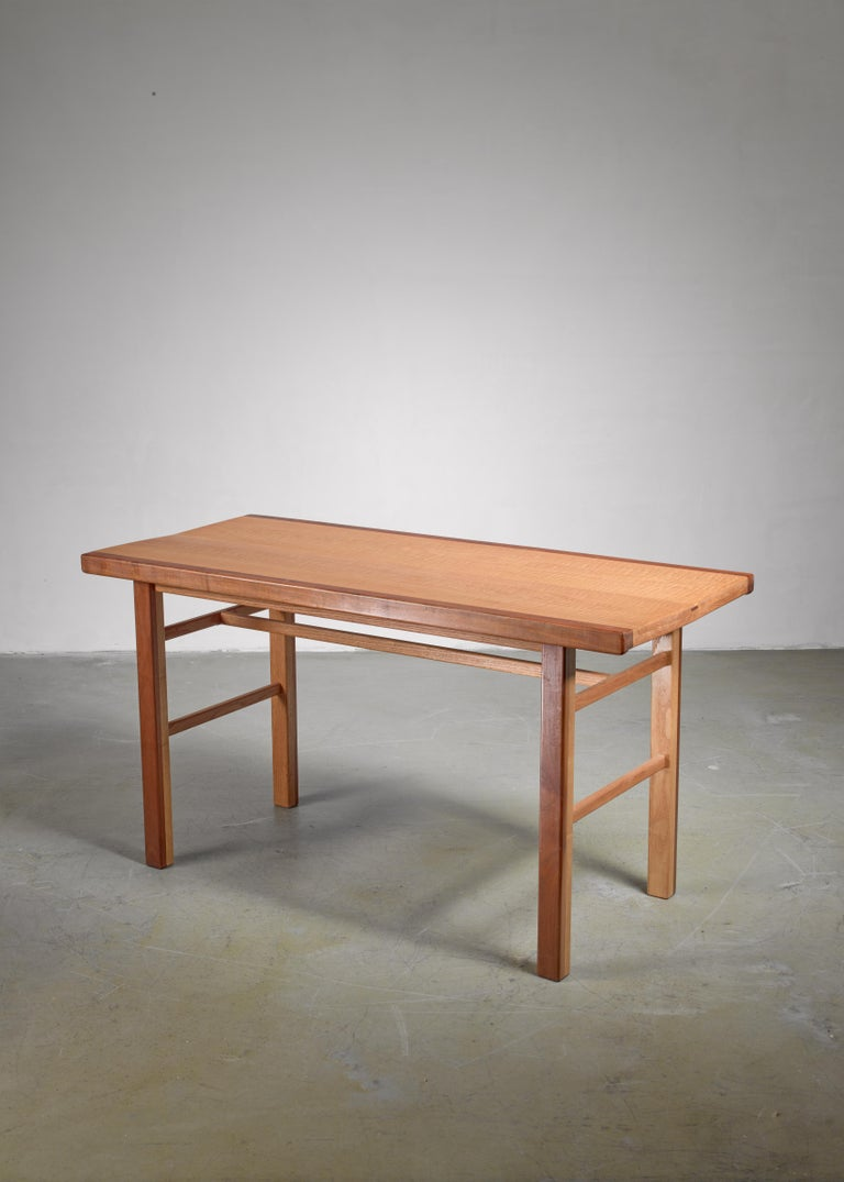 A studio crafted walnut and oak console table by American artist Gene Caples (1935 - 2015).  The wood is joined with pegs and by tongue-and-groove connections.